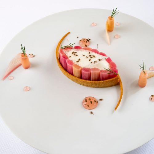 Pâte sablée à l'aneth de Bretagne renfermant une compotée de rhubarbe, de la rhubarbe pochée et une mousse de yaourt à l'aneth de Bretagne.